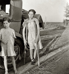Drought refugees on highway near Bakersfield, family of six, no shelter, no food, no money and almost no gasoline, the child has bone tuberculosis, by Dorothea Lange 1935