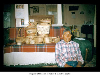 Charley Howeattle with a basket collection in a house on the Quileute Indian Reservation