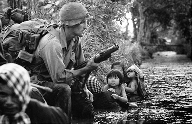 Two Vietnamese children watch a paratrooper as they huddle for protection against a canal bank near Saigon 1966, by Horst Faas
