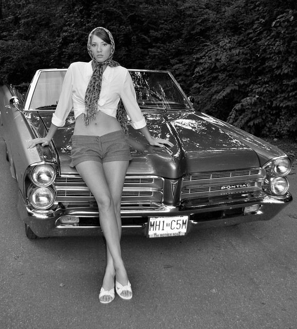 black & white photo of a 1965 Pontaic Convertiable with a girl leaning on the hood