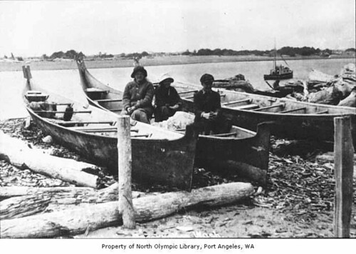 Three people, probably Native Americans, with canoes in La Push