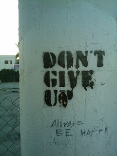 "The words ""Don't give up"" written in graffiti on a wall"