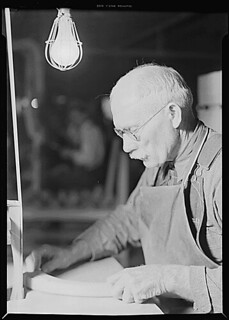High Point, North Carolina - Upholstering. Tomlinson Chair Manufacturing Co. Upright belt sander chair arm - been at the furniture business 30 years - man and machine in action, 1936 - 1937