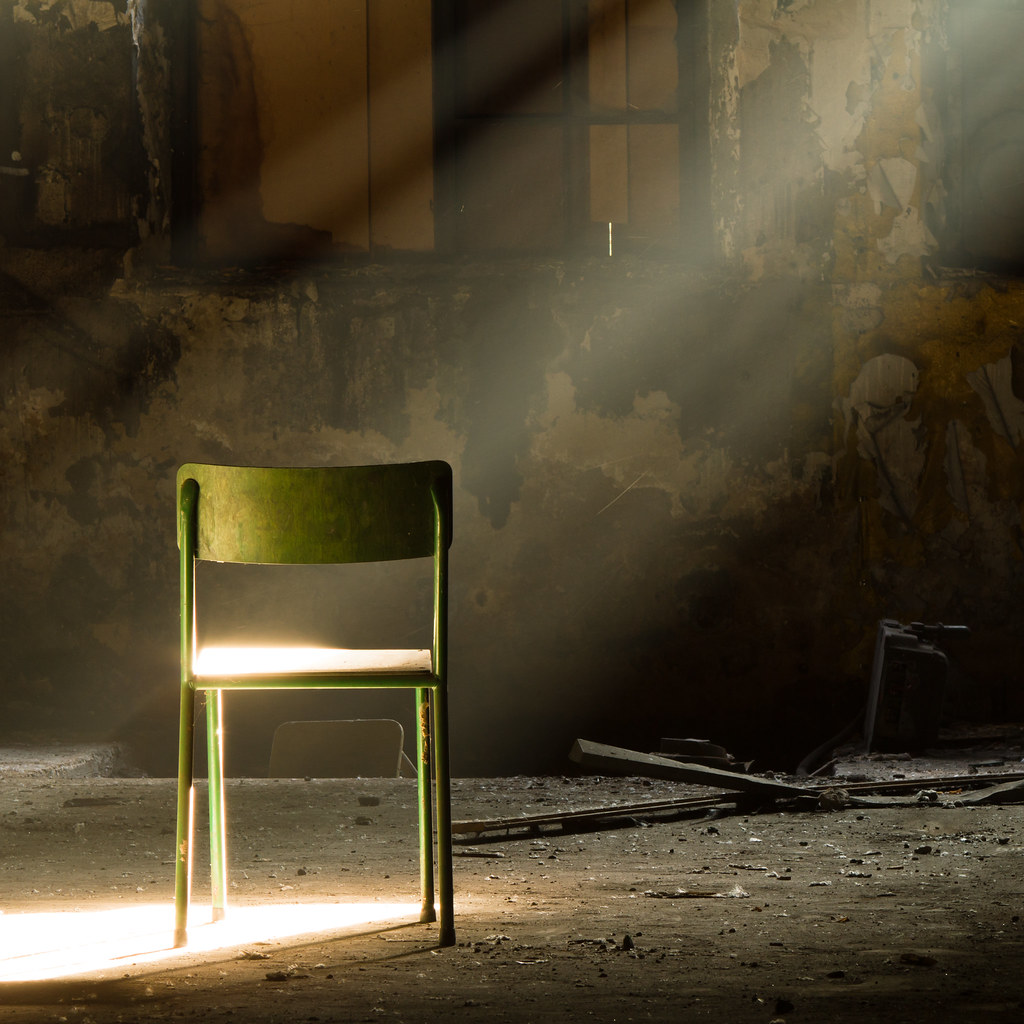 Dark room with light through window - A Lone Green Chair In A Dark Dirty Room A Ray Of Sunlight Shines Through
