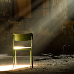 A lone green chair in a dark dirty room, a ray of sunlight shines through the window on the green chair