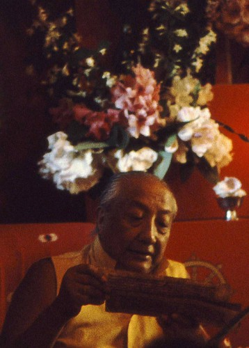 HH Dilgo Khyentse Rinpoche reading a pecha, giving an initiation, with a bouquet of flowers on the shrine behind him, Sakya Ward St Dharma Center, Seattle, Washington, USA 1976 by Wonderlane