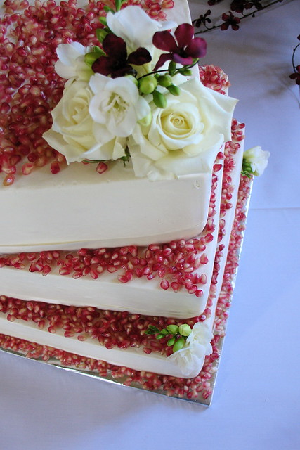 Red Velvet wedding cake decorated with pomegranate and white roses