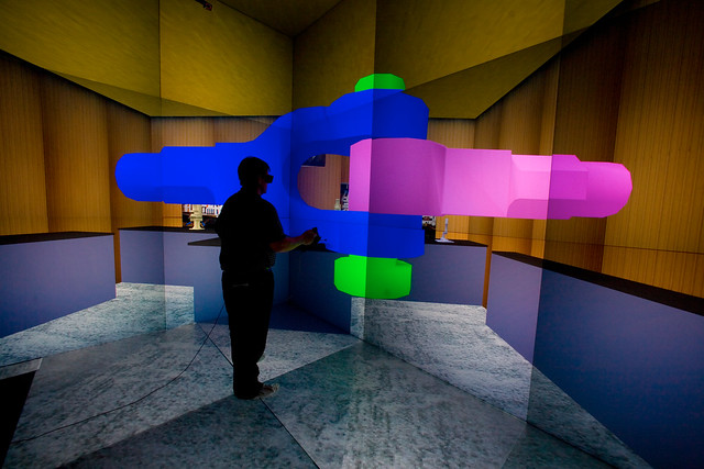 A user interactively assembles a mechanical joint inside a virtual environment in the CAVE. The glasses and hand-held wand are motion tracked to allow free movement of objects within the virtual world. This capability allows designers to test and validate design options, create and verify safety plans and provide training experience for workers. Over the past several years, Los Alamos National Laboratory has invested in providing state-of-the art facilities and software tools to help scientists in the Advanced Simulation and Computing (ASC) program understand and explore their data.   Photo by LeRoy Sanchez.