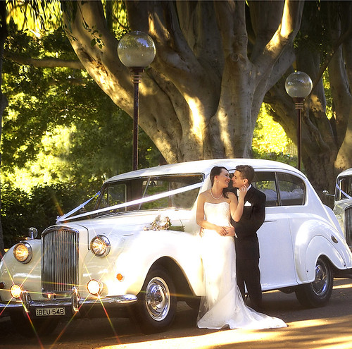The bride and groom in-front of a Princess car.