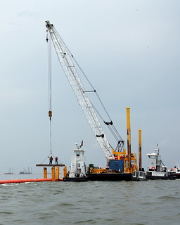Workers assemble 36 in pipe hard boom on Barataria Bay
