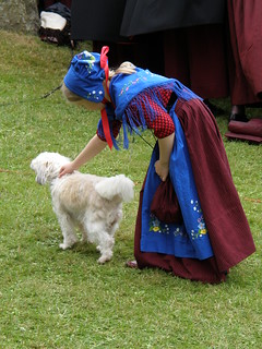 A little girl in Faroese National Costume playing with a dog at the Day of Ólavsøka 2009