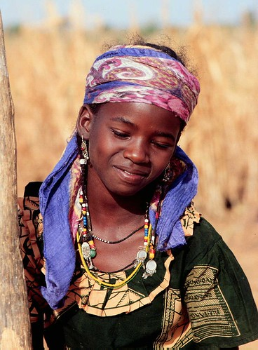 West African girl daily pounds grain for her family's daily meal