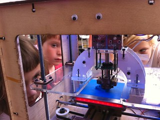 Kids surrounding the MakerBot at makerfaire by bre pettiss
