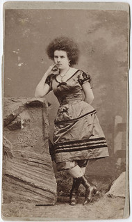 [Photograph of a circus performer; a woman leaning on a rock]
