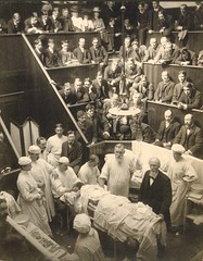A photo of Vincenz Czerny (1842-1916) with Dr. Levi Cooper Lane in a surgical amphitheater overseeing colleagues treating a laying on a table patient