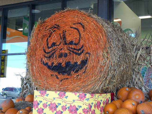 Jack-O-Lantern Painted On A Round Hay Bale.