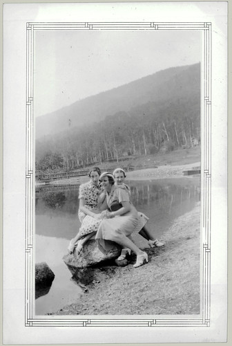 Three girls sitting on a rock