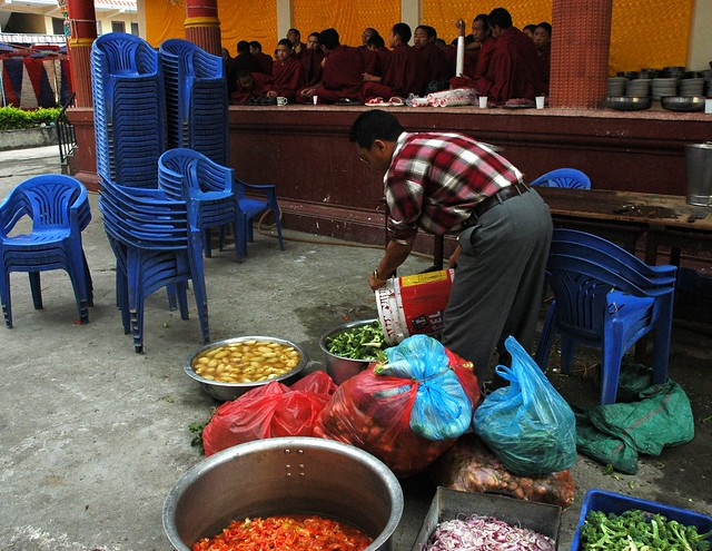 Cook preparing vegetables for dinner, monks on the Tharlam Monastery stage, blue stacked plastic chairs, red white and blue tents in the background, Boudha, Kathmandu, Nepal