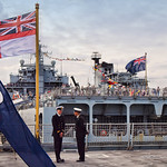 Portsmouth Navy Day visitors enjoy the view from RFA Argus behind Royal Navy officers on the flight deck of HMS Dauntless.