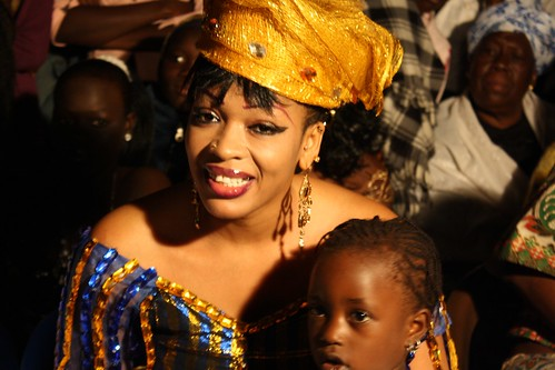 <p>Honored guest and famous Medina dancer and pop star Oumou Sow sits on the sidelines with neighbors.</p>
