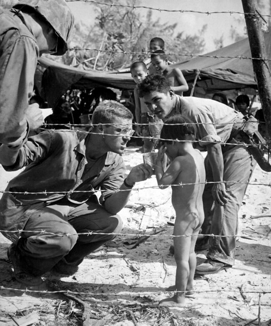Marines try to soothe a crying child by offering a shiny rations tin.  Children are sheltered with their families in a camp set up for refugees from battle areas by U.S. Marine Civil Affairs authorities on Saipan, July 1944, by Ted Needham