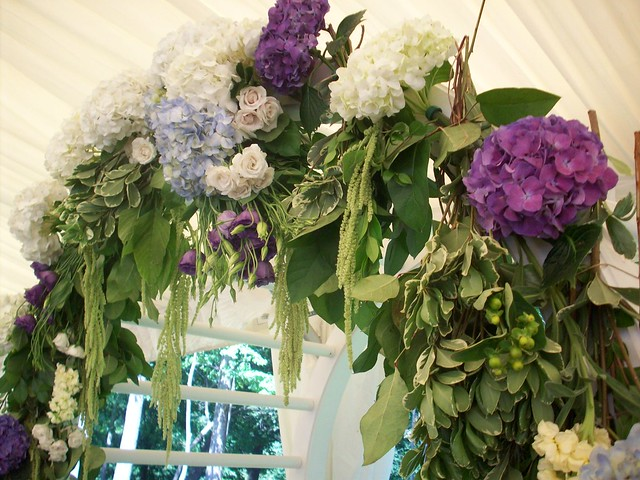 A wedding arch covered in blue white and purple flowers like hydrangea