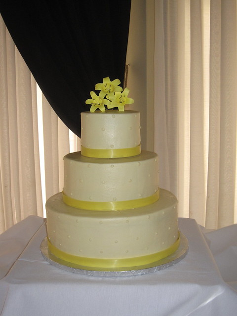 A 3tier round wedding cake with ribbon along the base and icing beading