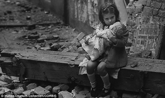 A young girl clutches her doll while sitting amid the rubble of her bombed-out home, London 1940
