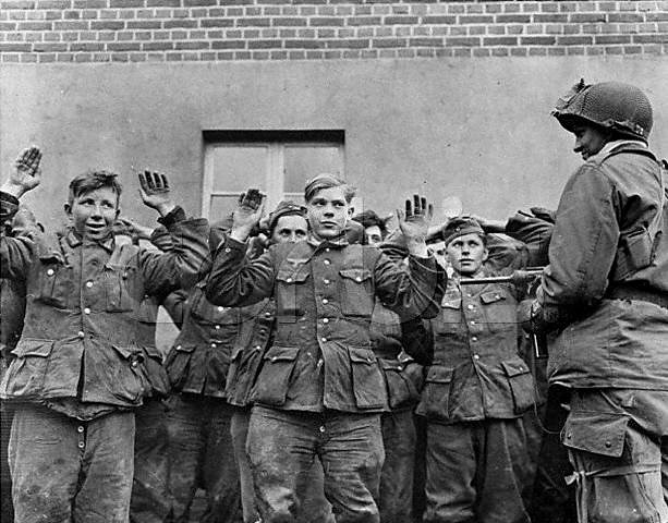 A soldier, probably American, holds a gun on a group of teenaged German soldiers, who hold up their hands more in relief than fear, Germany ca. 1944-45