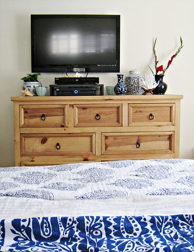 large rustic dresser+blue and white floral bedding+mounted flatscreen tv+porcelain vases