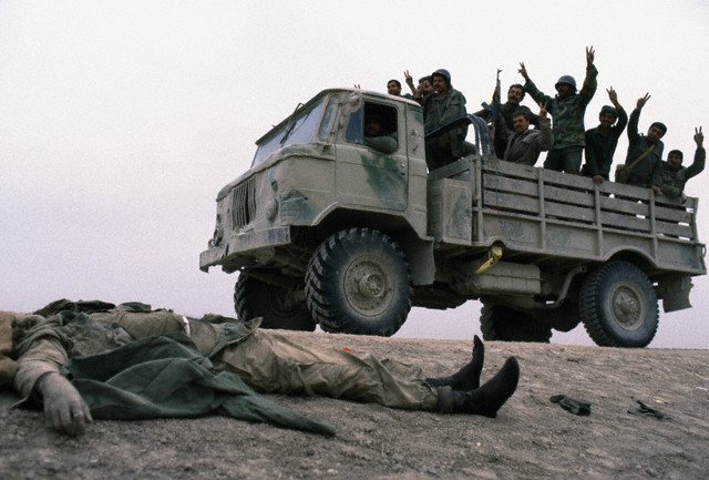 Iraqi soldiers on the southern front rejoice as they pass in front of the body of a dead Iranian soldier after fighting took place around Basra, by Jacques Pavlovsky 1985