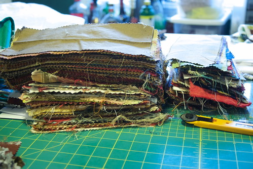 It turns out you can remove the labels from most upholstery and drapery samples by heating them with a dry iron for a few seconds. Hello large pile of usable fabric.
