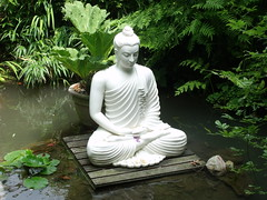 flower(0.0), fictional character(0.0), jungle(0.0), garden(1.0), monument(1.0), gautama buddha(1.0), sitting(1.0), statue(1.0),