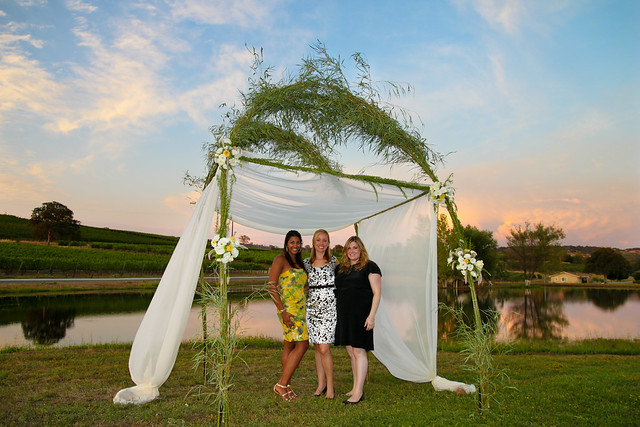 A few friends stop for a picture under a wedding trellis at sunset