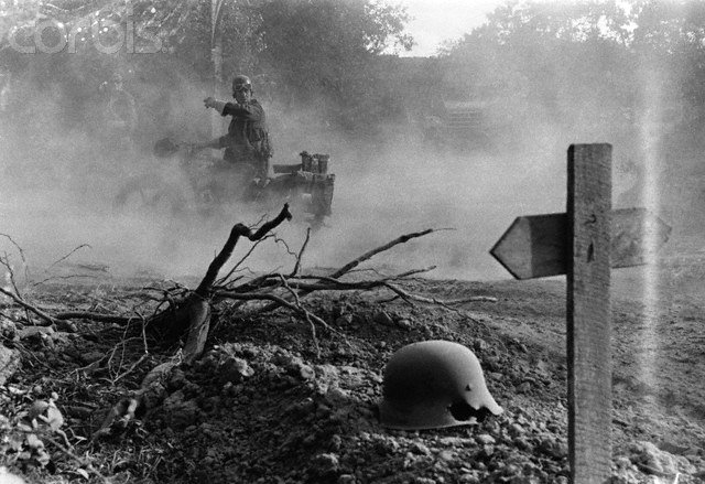 British columns ride forward in pursuit of retreating Germans, past a makeshift German grave, marked by a shrapnel torn helmet and a rough wooden cross, by Leonard McCombe 1944