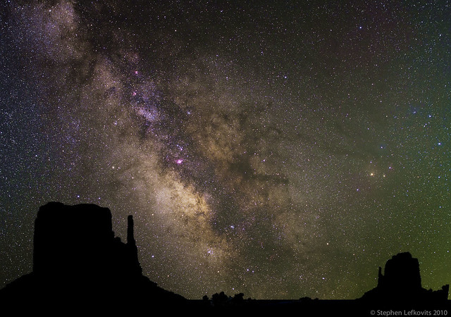 Five minutes of exposure of the Milky Way composited with a Monument Valley silhouette.