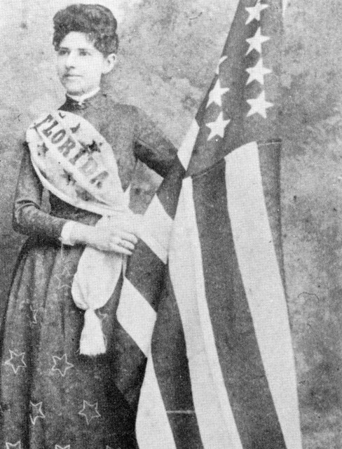Mena E. Williams Hirshberg stands by a U.S. flag: Tallahassee, Florida
