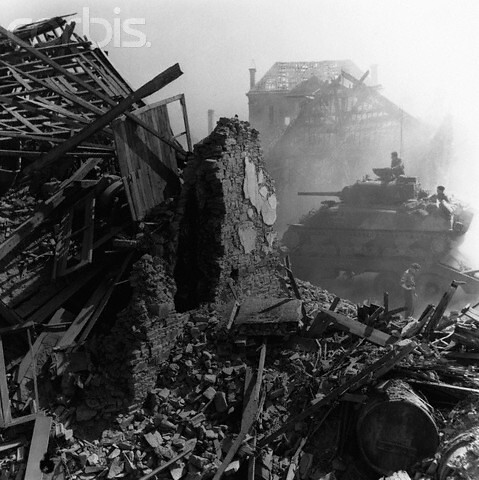 In support of the infantry, a British tank rumbles through a devastated Normandy village, by Leonard McCombe 1944