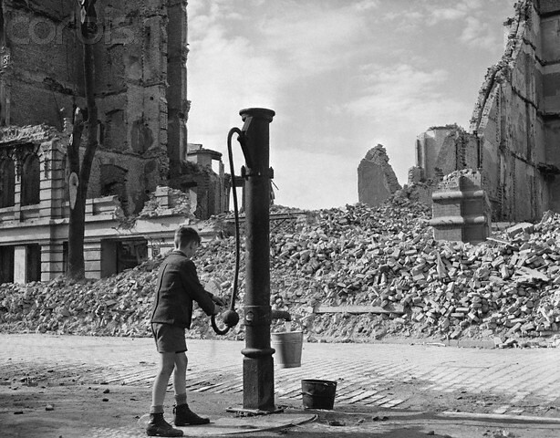 Magdeburg, Germany, A German boy draws water from a pump after the water supply was destroyed in Magdeburg by bombing and shelling by the 30th infantry division, 9th US Army, April 1945