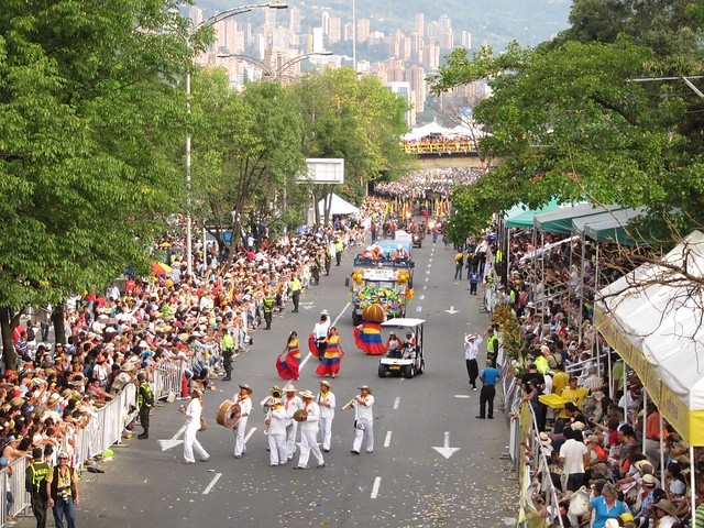 A marching band and women wearing the colors of the Colombian flag.
