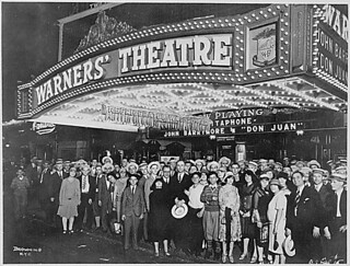 "First-nighters posing for the camera outside the Warners' Theater before the premiere of ""Don Juan"" with John Barrymore, Washington DC, 08/06/1926."