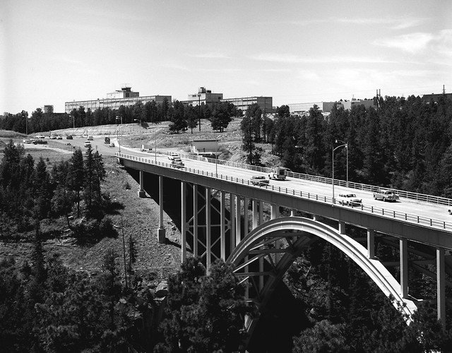 Historical photo from Los Alamos National Laboratory (LANL). Sixties-era vehicles cross Los Alamos Canyon via the LA bridge, also known as the Omega bridge. The horizon is dominated by the original mid-fifties Administration Building.
