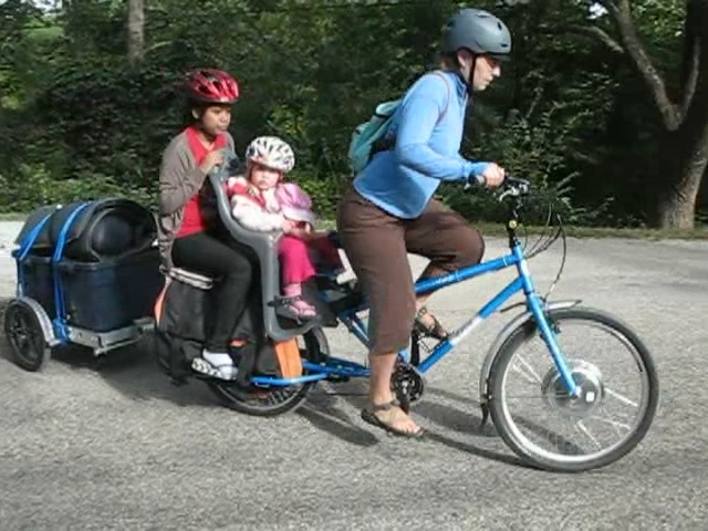 Electric Yuba Mundo cargo bike with two kids and trailer