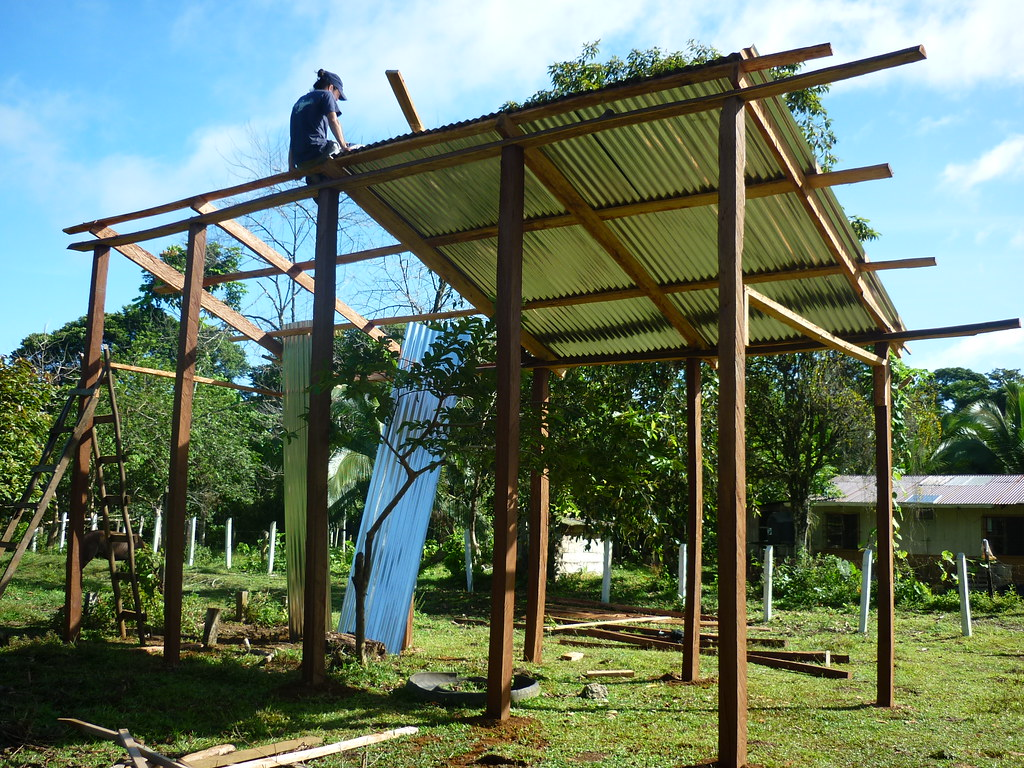 Panthera Field Scientist, Daniel Corrales, is shown sitting on top of a beam as he helps set aluminum sheets as the roof of the enclosure.   Read 'Panthera's Guide to Building a Livestock Corral' from our October 2010 newsletter at www.panthera.org/november-2010-newsletter.  Learn more about the work Panthera's Costa Rica team is doing at pantheracostarica.org/.   Also read about our jaguar conservation work in other countries through our Jaguar Corridor Initiative - www.panthera.org/programs/jaguar/jaguar-corridor-initiative - and Pantanal Jaguar Project - www.panthera.org/programs/jaguar/pantanal-jaguar-project.    © Josephine Dusapin