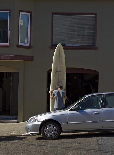 Man with long surfboard; The Richmond, San Francisco (2011)