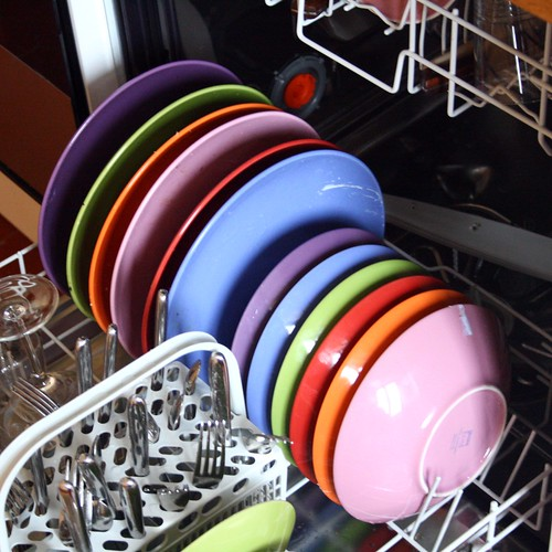 lavastoviglie aperta con piatti colorati disposti al suo interno