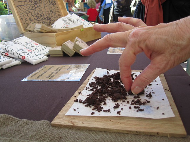 A visitor takes a taste of Fine & Raw Chocolate at the Chile Pepper Fiesta. Photo by Dave Allen.