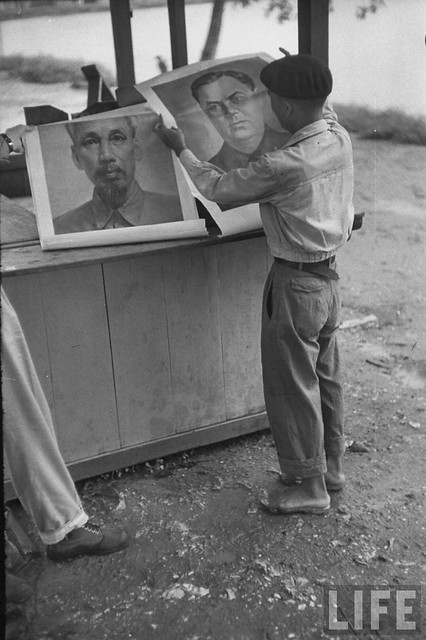 Man looking at posters of new leaders shortly before Communist takeover of city from the French. Oct 1954