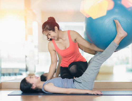 Asian woman fitness coach teach her student for rubber ball exercise