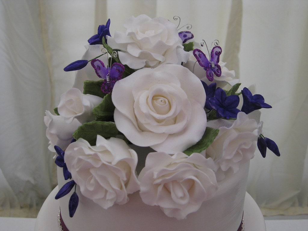 purple wedding cake with sugar flowers and butterflys a